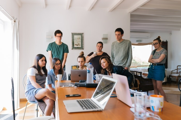 パソコンの前で談笑する若い男女達